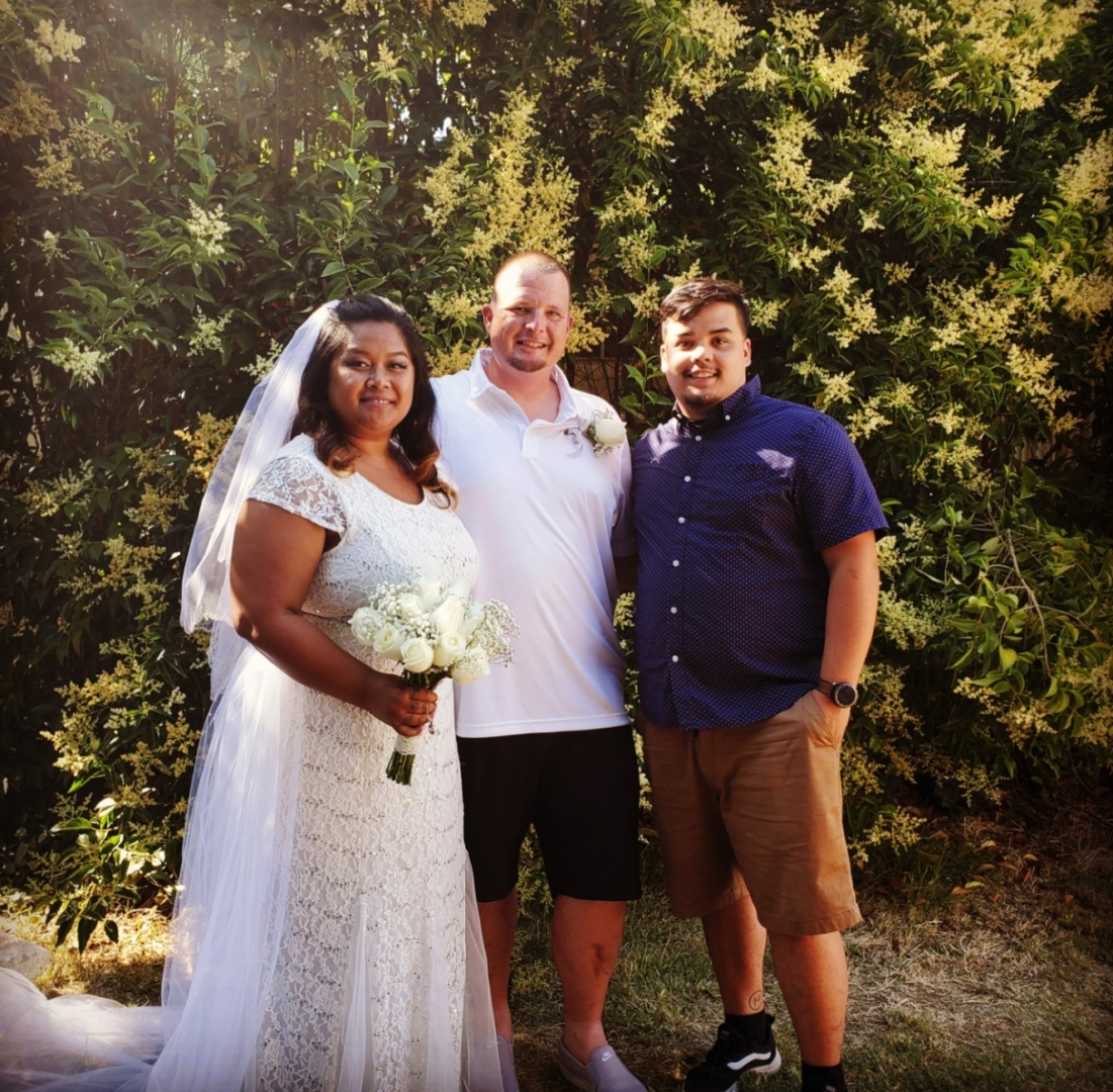 Lobsien stands with a bride and groom, his longtime mentor.