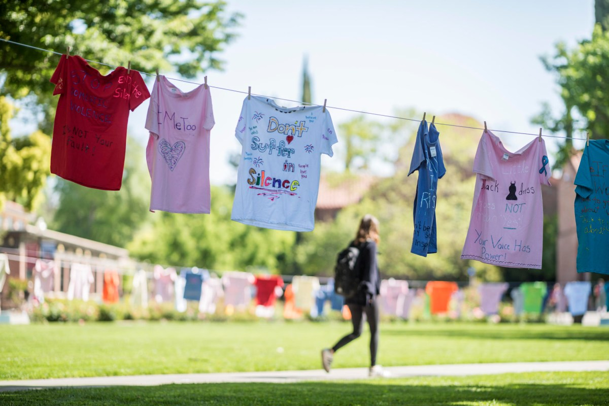 """T-shirts hang on campus with messages like """"don't suffer in silence"""" and """"#metoo"""" and """"stop domestic violence. it's not your fault."""""""