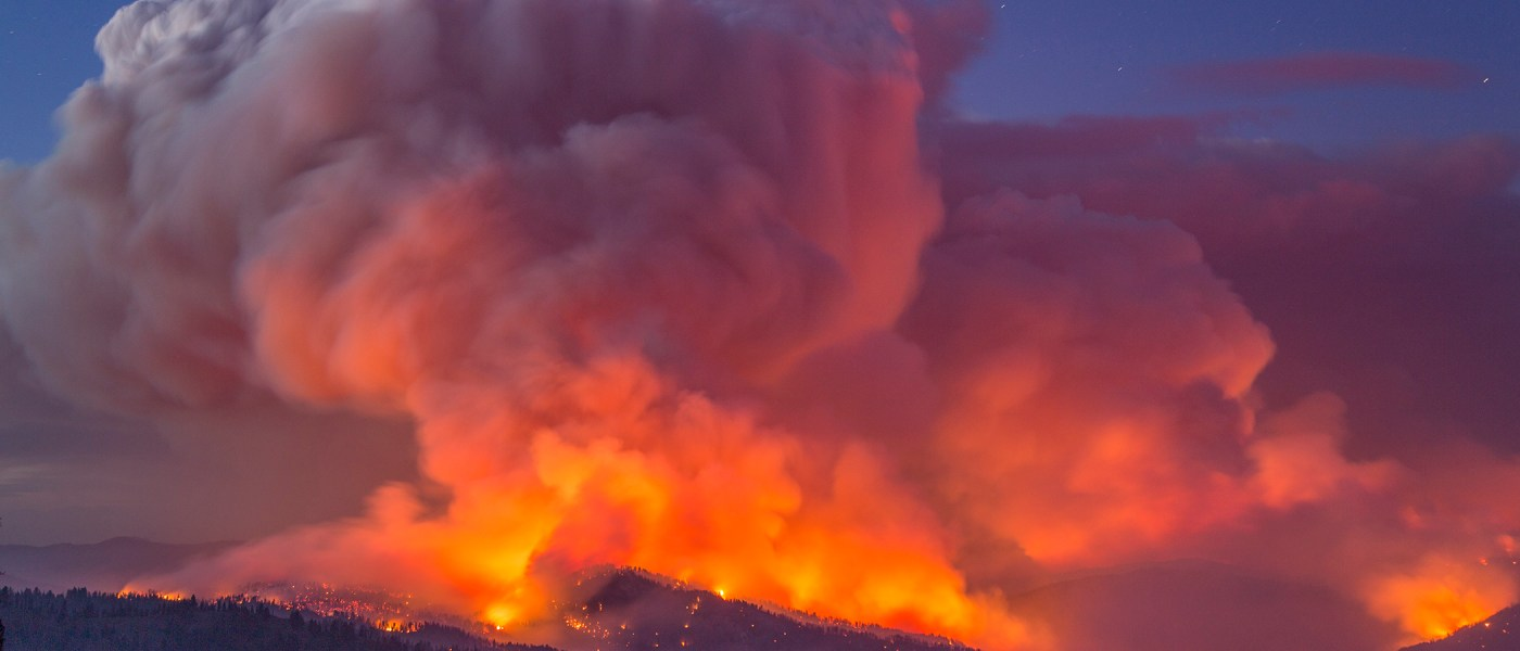 A giant smoke column is seen exploding from flames on a darkened hillside as a wildfire rages out of control.