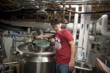 """Josh Leavy smiles as he brews Resilience IPA in a container reading """"San Francisco Brewing Co."""""""