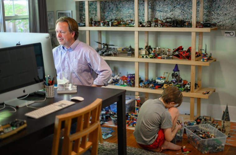A faculty member addresses his class on his laptop, while his son assembles Legos on the floor behind him.