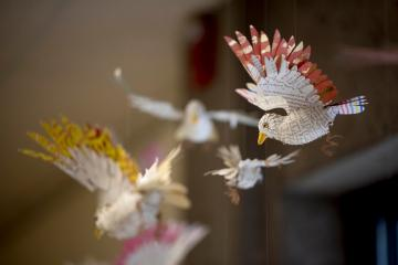 Small sculptures of flying birds, made out of book pages and colored paper, hang from the ceiling.