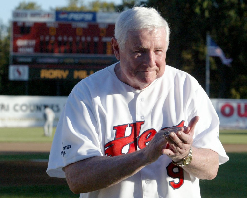 Steve Nettleton wears a Chico Heat jersey and applauds while standing on the field at Nettleton Stadium.