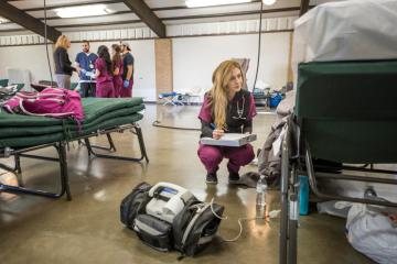 A nursing student crouches down to help a patient at an evacuation center during the Oroville Dam crisis in February 2017.