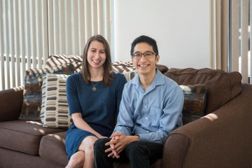 Joe Liu and his wife Danielle pose for a picture while sitting together on the couch.