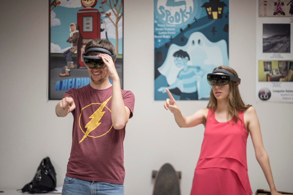 Computer Animation and Game Development (CAGD) student  Tony Alessio (left) and Media Arts, Design and Technology (MADT) Sarah Rose Vaughn (right) wear a Microsoft HoloLens.