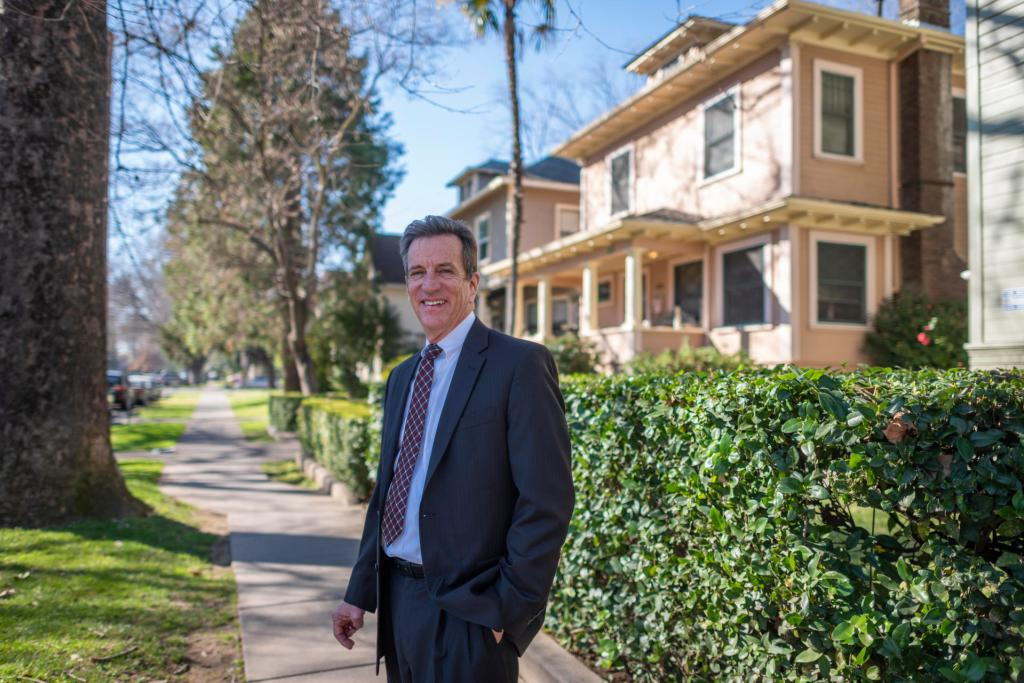 Dan Herbert smiles while standing in a neighborhood of student housing.