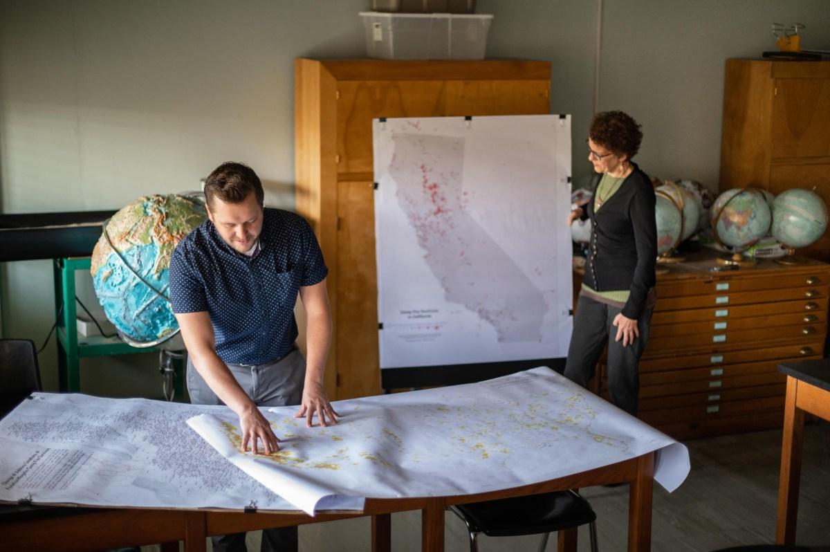 Peter Hansen and Jacque Chase look at maps on a table and on a cabinet.