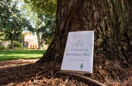 "This year's Book in Common, ""In Search of the Canary Tree,"" rests against a tree outside Kendall Hall on a sunny spring day."
