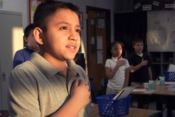 Elementary school students stand in a classroom with their hands over their hearts as they recite the Pledge of Allegiance.