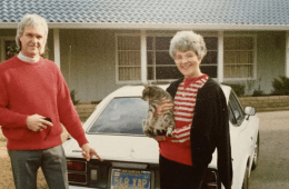 Ladd Johnson and a woman holding a cat stand next to a car outside a home.