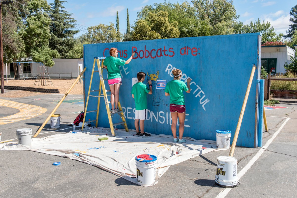 Students paint a mural on a backboard for playing ball at Citrus Elementary.