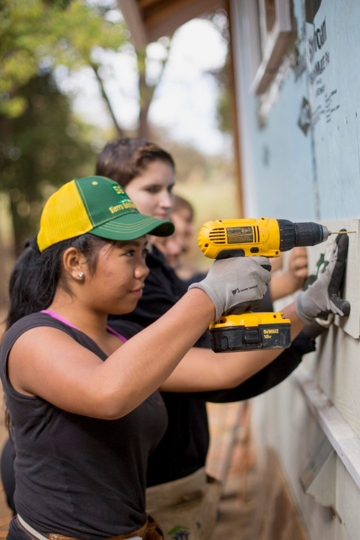 A student uses a battery-powered drill to install siding on a house.