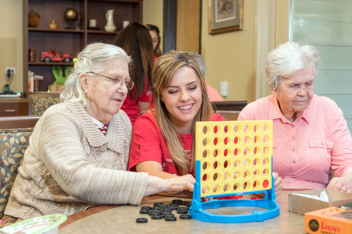 A student plays Connect Four with senior citizens at an assisted living facility.
