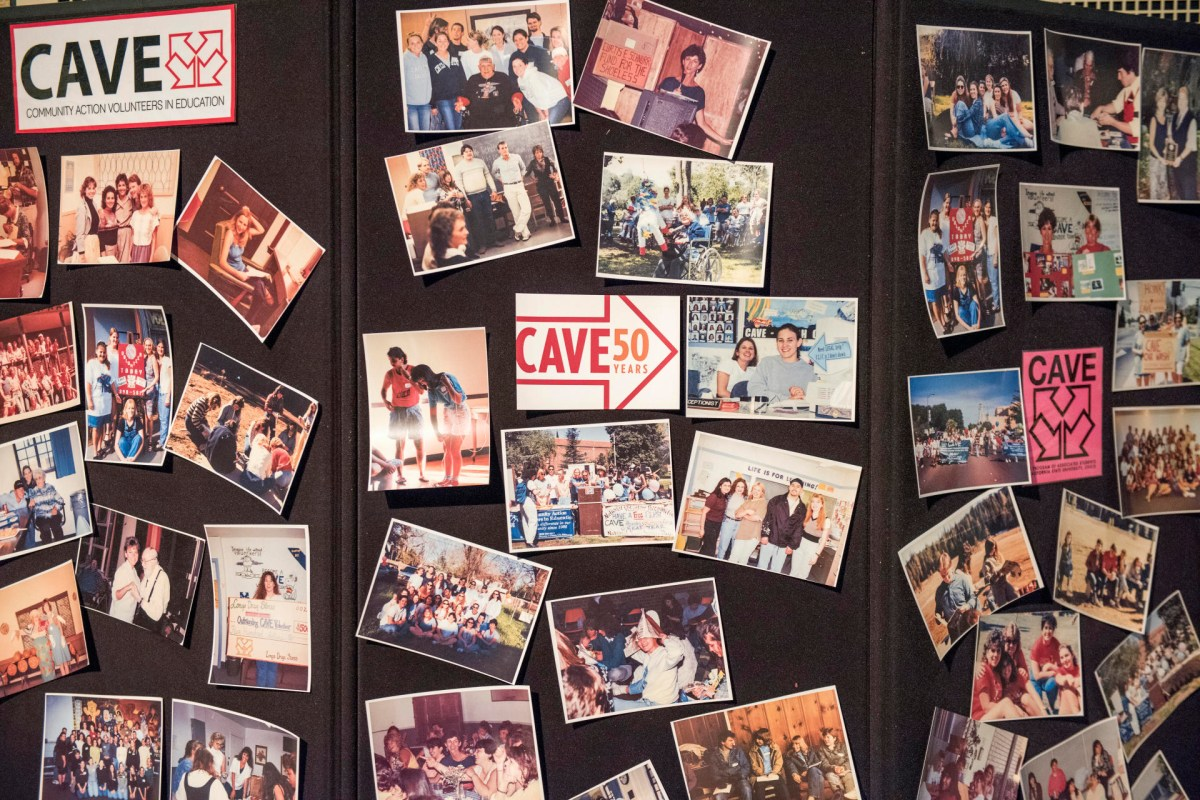 A collection of CAVE photos across the decades are tacked onto a tri-fold poster board.