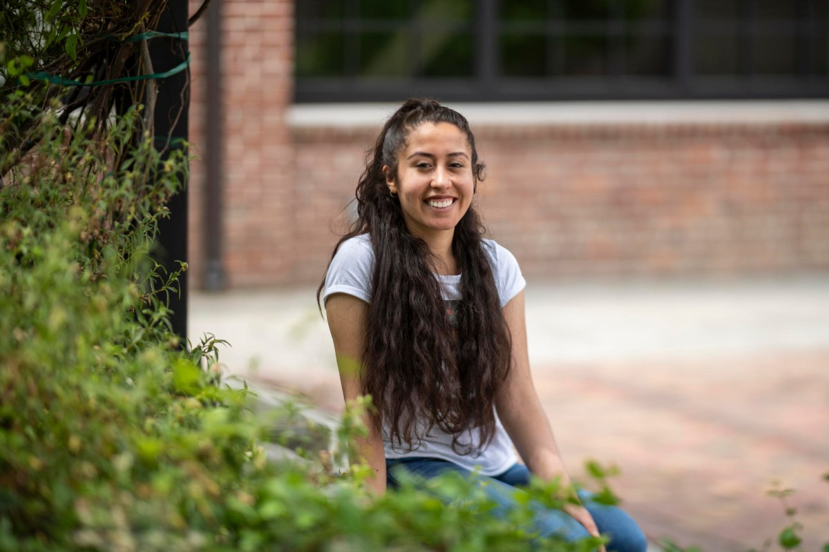 Chico State student Angela Serrano sits on a bench outside brick-lined Colusa Hall.