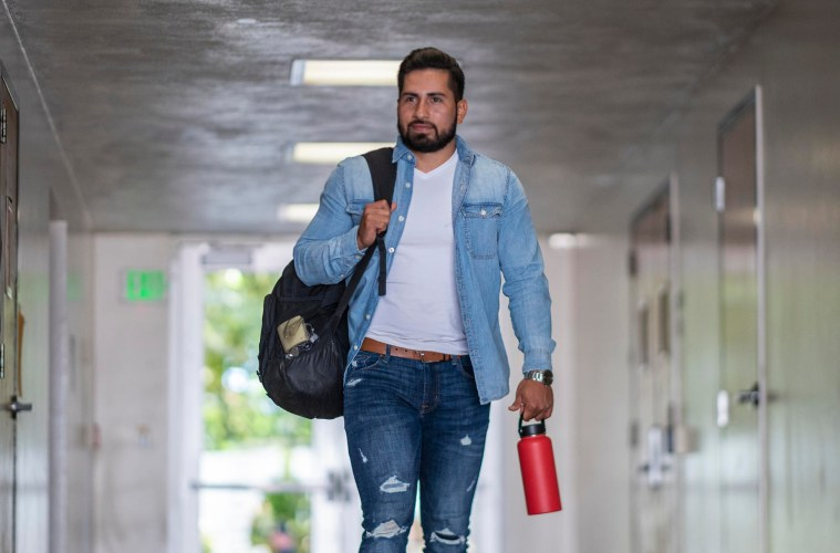Jaime Valdovinos walks through an outdoor hallway on campus carrying his back and reusable water bottle