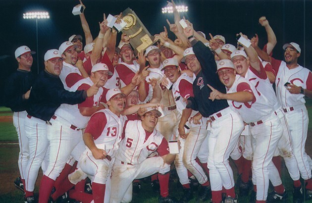 The 1999 baseball team holds up the national trophy and cheers after winning.