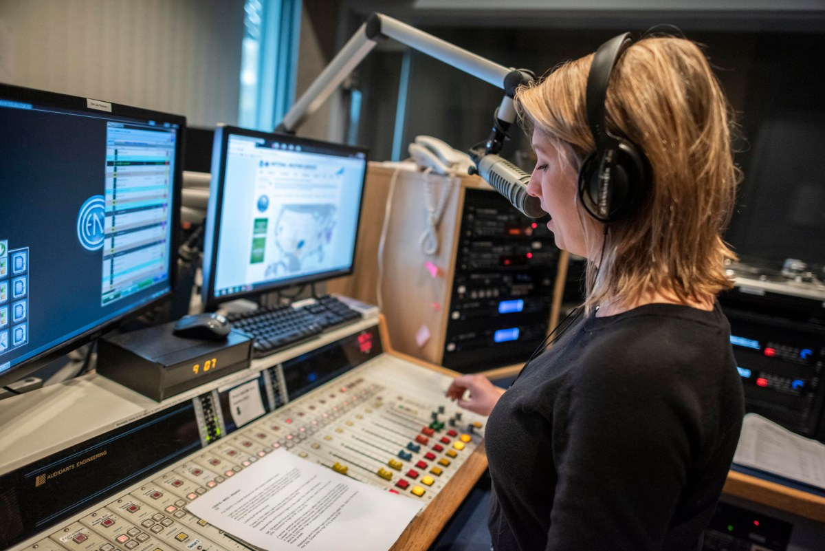 Sarah Bohannon wears headphones as she reads from a script on the radio control board, with two computer monitors in front of her.