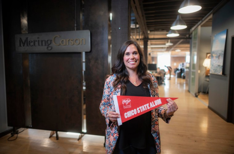 Michelle McIntosh smiles and holds a Chico State alum pennant at her Mering Carson office.