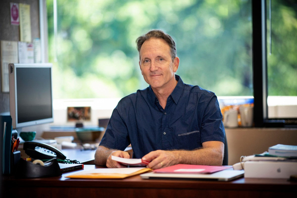 Al Schademan sits at a desk in his office with a book in his hands.