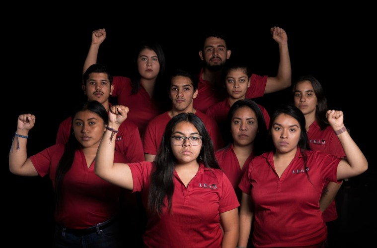 A group of students involved with the Dream Cente raire their fists in show of solidarity and support while all wearing red polos.