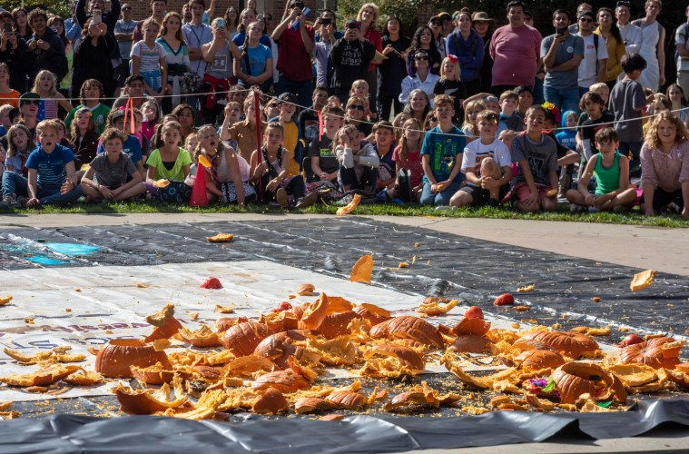 Elementary school students gasp and smile in delight as pumpkins are smashed into a big mess.