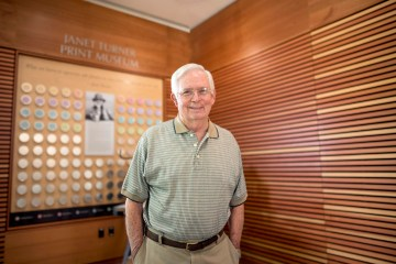 Michael Halldorson poses for a portrait in the Janet Turner Print Museum, with a portrait of Turner behind him.