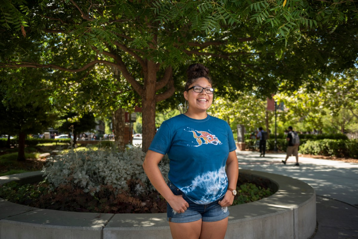 Jacklynn Rodriguez smiles and stands in front of a tree planter box on campus