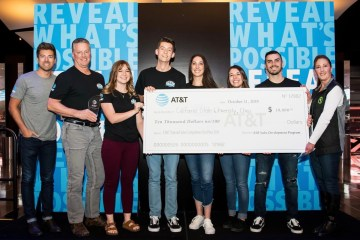A row of students hold an oversized check given as a first-place prize.