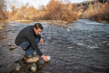 Jackson Webster dips a sampling container into Butte Creek.