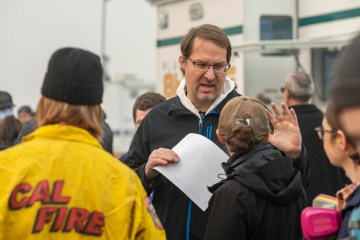 Eric Bartlink speaks to a colleague under smoke-filled skies at the command center for Camp Fire response.