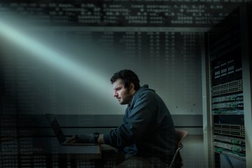 A student sits at a computer with dramatic lighting streaming in from a window.
