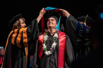 A graduate student basks in the glory during her Commencement ceremony.