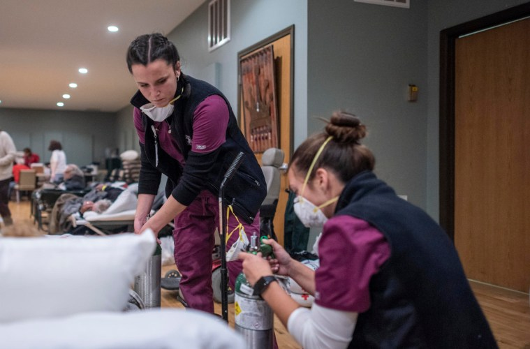 Chico State nurses wearing scrubs and masks attend to patients.