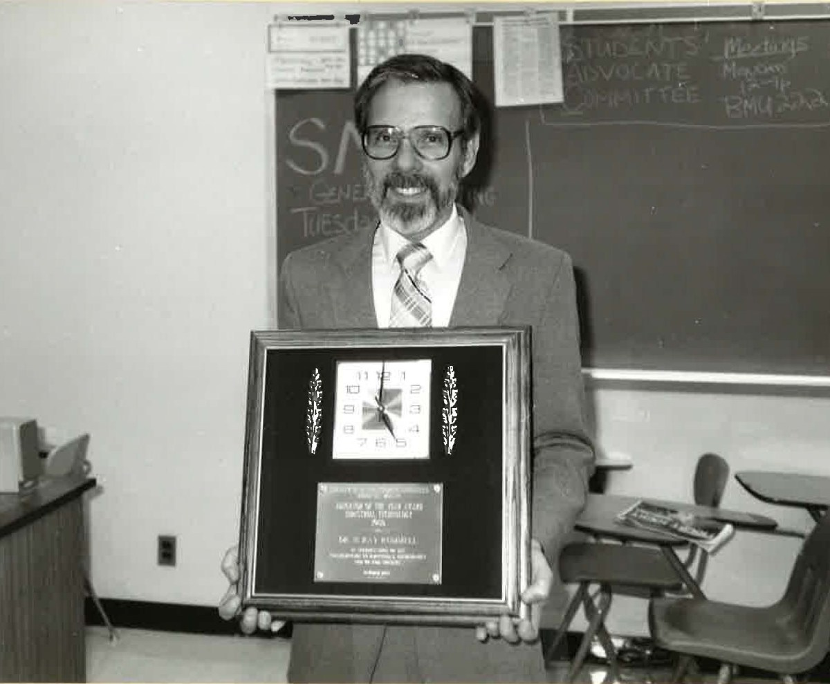 Ray Rummell stands with a framed award.