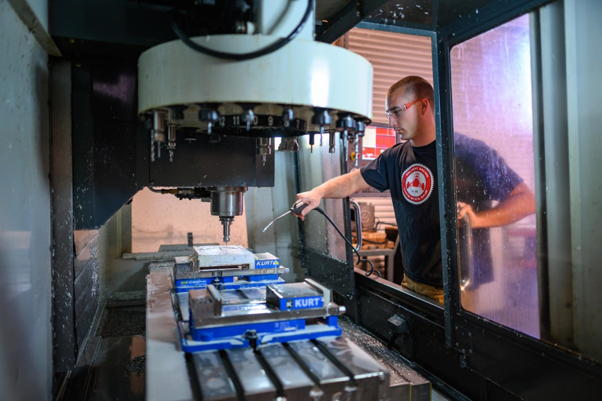 Perry Cheney works on a machine to make a mold to use for plastic injection.