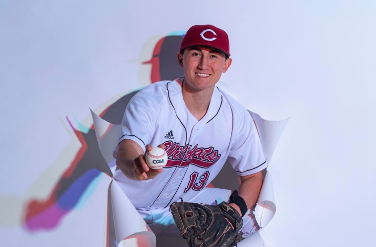 Tyler Stofiel breaks through a white photo backdrop in his uniform and a baseball in hand.