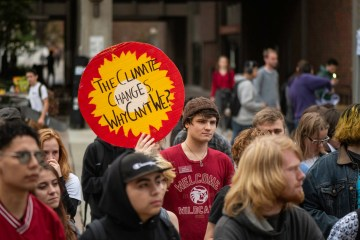A student holds up a climate change protest sign during a group demonstration on campus