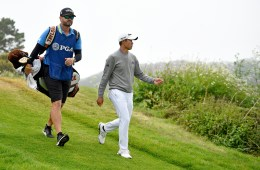 JJ Jakovac walks on a golf course with Collin Morikawa.