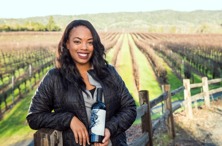 Brenae Royal holds a bottle of wine with a vineyard in the backdrop
