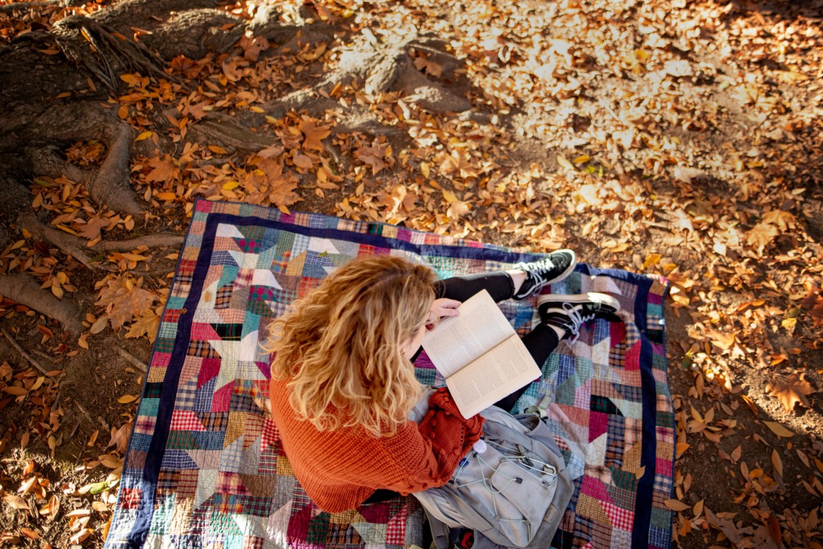 A student sits on a quilted blanket as she reads a book that is opened on her lap.