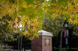 A brick pillar with a University seal stands out amongst trees and leaves changing colors.