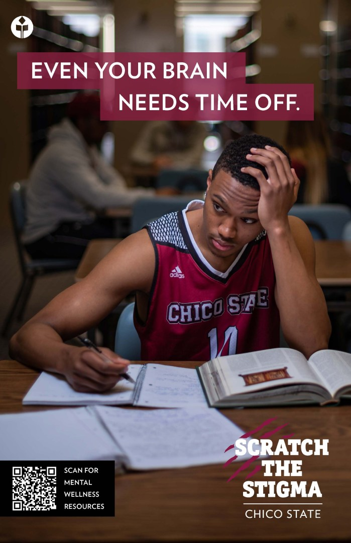 A basketball player sits with his head on his head as he works in a notebook in the library.