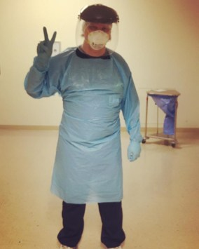 Jared Axen flashes the peace sign with his hand while dressed in scrubs, a protective gown, rubber gloves, a face mask, and a face shield.