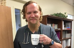 Jared Axen holds a mug while dressed in his scrubs and a stethoscope around his neck.