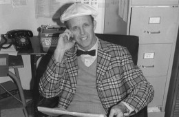 John Sutthoff sits in a chair reading a paper in a bowtie and newsboy cap.
