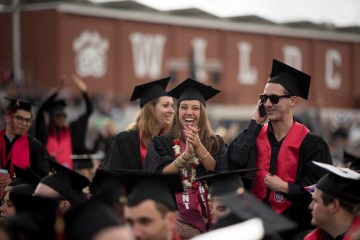 College graduates dressed in graduation regalia celebrate.