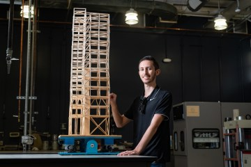 Jordan Beach smiles while inspecting a wooden skyscraper model