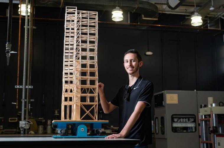 Jordan Beach smiles while inspecting a wooden skyscraper model